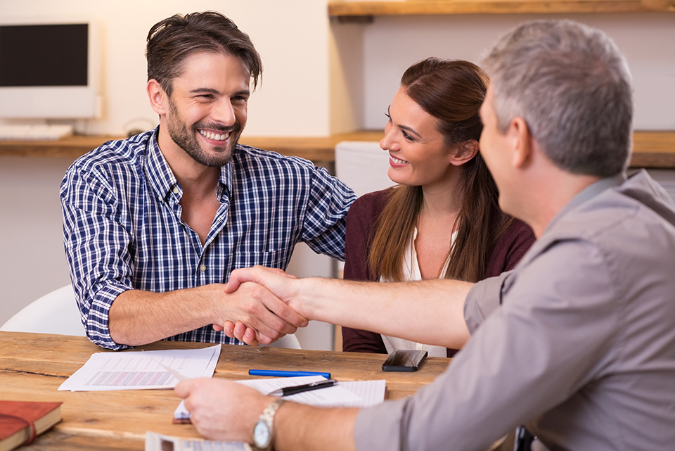 Smiling couple shaking hands with loan officer