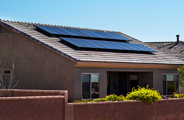 Photo of solar panels on red tile roofed house