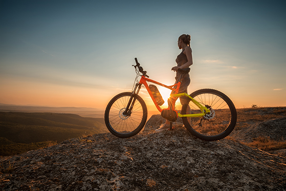 Woman with electric bike viewing sunset in the desert