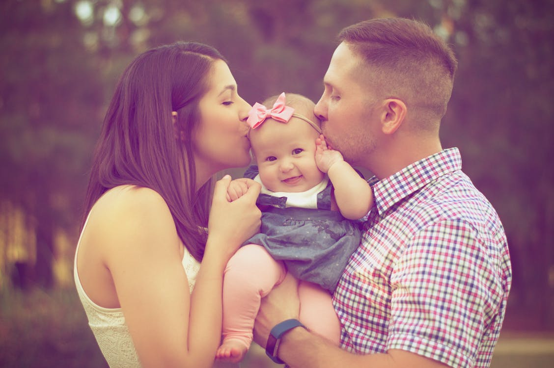 Photo of young couple kissing baby